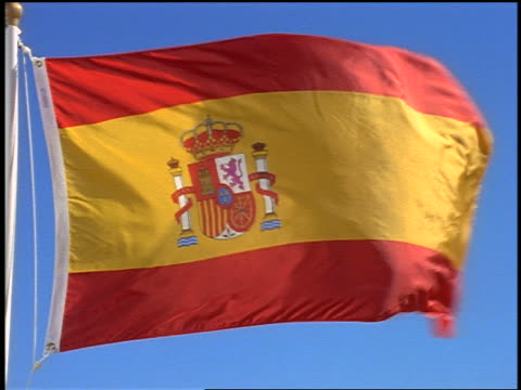 close up zoom out Spanish flag blowing in wind / blue sky in background