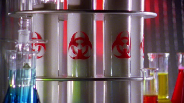 close up zoom out test tubes w/biological microorganism hazard logo and colored chemicals - biohazard symbol stock videos & royalty-free footage