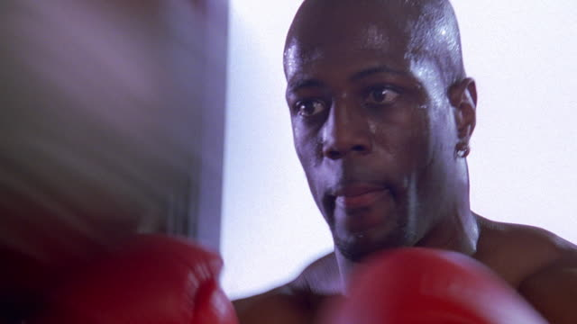close up zoom out to ms shirtless black male boxer sparring with speed bag in gym - shirtless stock videos & royalty-free footage