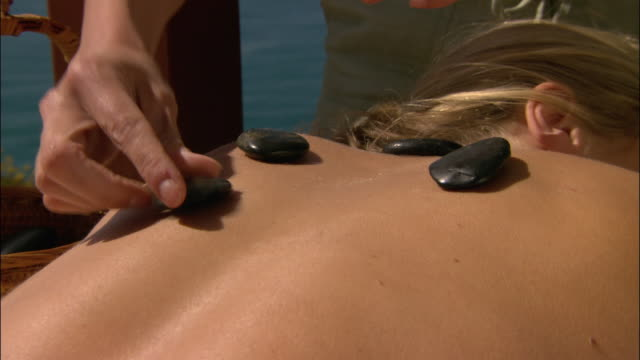 vídeos de stock e filmes b-roll de close up zoom out woman getting hot stone treatment with ocean in background/ monterey county, california - terapia lastone