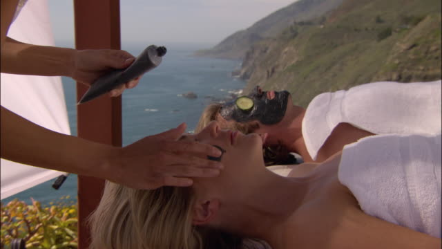 vídeos de stock, filmes e b-roll de close up zoom out woman giving couple mud masks with ocean in background/ monterey county, california - mesa de massagem