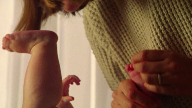 vídeos de stock, filmes e b-roll de close up zoom out woman tickling feet of baby in nursery - fazendo cócegas