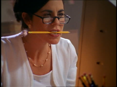 close up zoom out woman wearing reading glasses with pencil in mouth working on computer - businesswoman stock videos & royalty-free footage