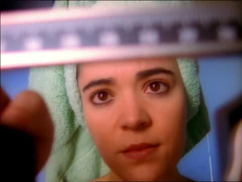 stockvideo's en b-roll-footage met close up zoom out woman with towel wrapped around head weighing herself on scale and getting excited with result - alleen één mid volwassen vrouw