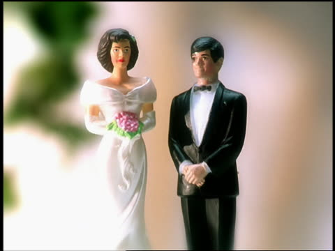 close up zoom out woman's hand turning miniature plastic groom upside down on wedding cake with mini bride to side - 離婚点の映像素材/bロール
