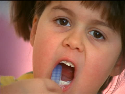 close up zoom out young girl brushing teeth looking at camera - haarzopf stock-videos und b-roll-filmmaterial
