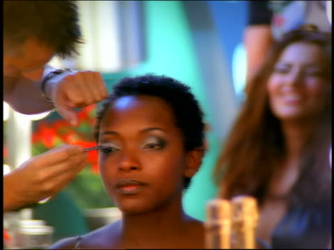 close up zoom out zoom in rack focus makeup artist putting eyeshadow on black model in mirror / 2nd model talking in background - fashion show stock videos & royalty-free footage