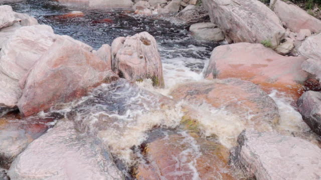 close up/pan left: bubbling waves flowing over white and pink rocks in stream in chapada, brazil - bach stock-videos und b-roll-filmmaterial