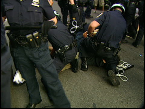 Close ups of a man being arrested and handcuffed on the ground and then dragged away by police during the 2004 antiwar protests in NYC Protestors...