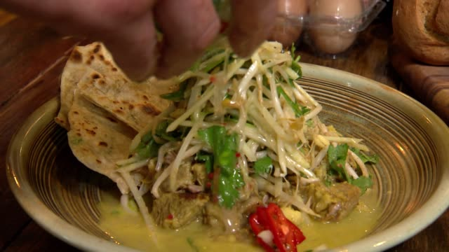 Close ups of hands adding papaya salad to green pork curry and flatbread / various close up shots of the whole and parts of the dish