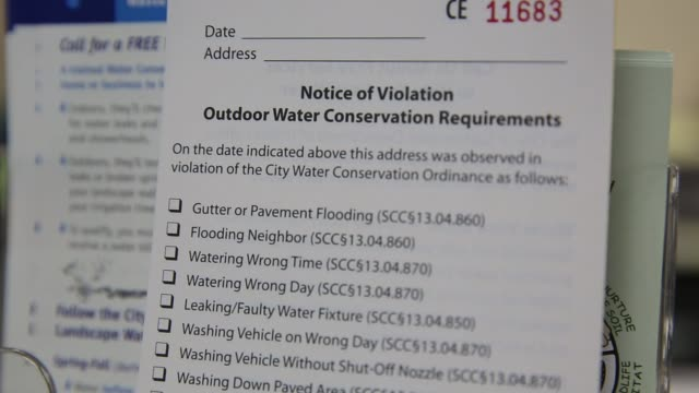 vídeos de stock, filmes e b-roll de close ups of pamphlets and questionaires promoting water conservation at the office of water conservation in sacramento california on june 5th 2015... - conservação da água