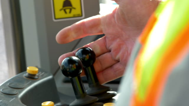 close ups on hands and the controls as a man operates a large loader. - earth mover stock videos & royalty-free footage