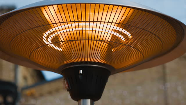 close view: electrical infrared patio heater against with blurry background - heizung stock-videos und b-roll-filmmaterial