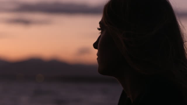 Close view from the side of young womans face at sunset