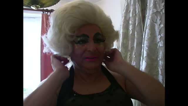 close view of a man putting a wig on in preparation for a pride event taking place in brighton, uk, in 2000. - adult stock videos & royalty-free footage