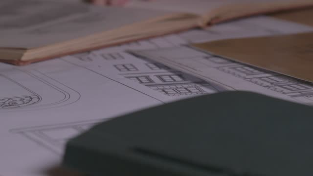 close view of hands sifting through architectural drawings - rebuilding stock videos & royalty-free footage