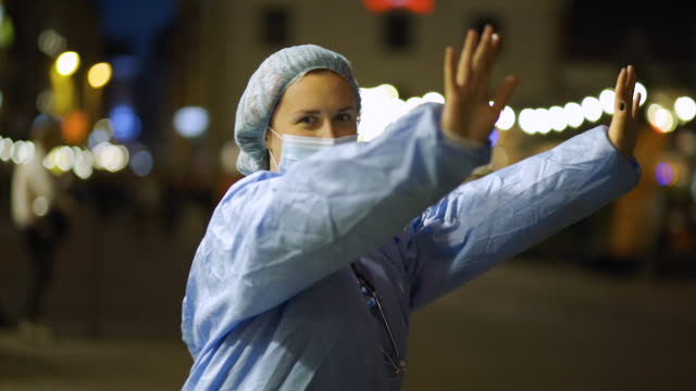 close view of happy doctor or nurse dancing in city centre to celebrate end of pandemic - surgical cap stock videos & royalty-free footage
