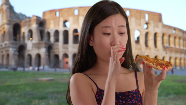 vídeos y material grabado en eventos de stock de close view of millennial woman eating pizza in front colosseum in rome italy - romano