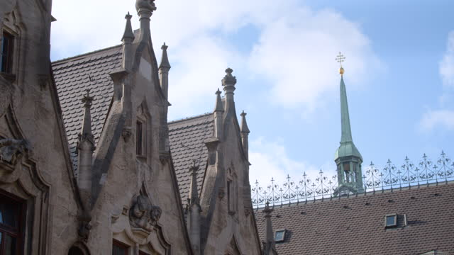 close view of new townhall inner courtyard roof with new gothic statues and st peters church tower in background - ペディメント点の映像素材/bロール