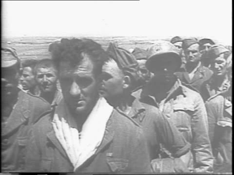 close view of prisoners as they start down a road / prisoners walk through town past sign 'siracusa centrale' / prisoners are guided along a road by... - anno 1943 video stock e b–roll