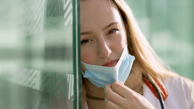 close view of sad female doctor or nurse in white medical gown taking off surgical mask - hospital gown stock videos & royalty-free footage