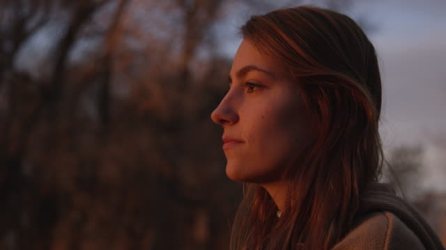 Close view of teenage girls face during sunset at she looks around
