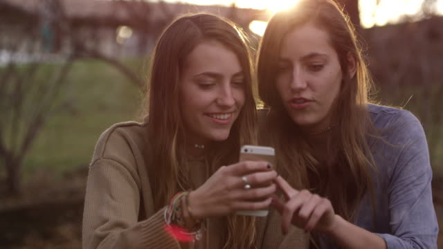 close view of two teenage girls looking at one smartphone - handhaben stock-videos und b-roll-filmmaterial