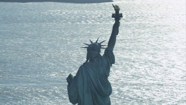 close view of upper part of statue of liberty from the rear. bright sun glare on statue and water below. shot in 2011. - artbeats stock videos & royalty-free footage