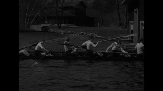 close view of wellesley college crew members in racing shell rowing backwards from dock on lake waban / another angle of crew members rowing shell... - wellesley massachusetts stock videos and b-roll footage