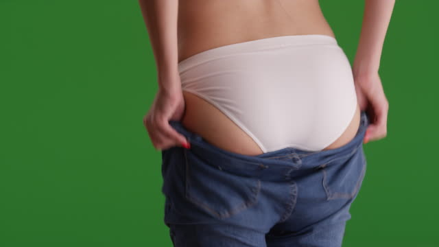 vídeos de stock e filmes b-roll de close view of young attractive woman in blue jeans in front of green screen - calças de ganga