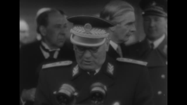 Close view of Yugoslavian Pres Josip Tito speaking Secretary of State for Foreign Affairs Anthony Eden standing behind him to his left