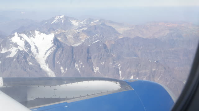 Close view out of an aircraft which is flying over Santiago de Chile overlooking the snowy mountain tops of the Andes