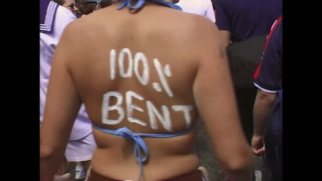 close view showing the back of a woman who has had '100% bent' written on her back in order to participate in a pride event taking place in brighton,... - one woman only stock videos & royalty-free footage