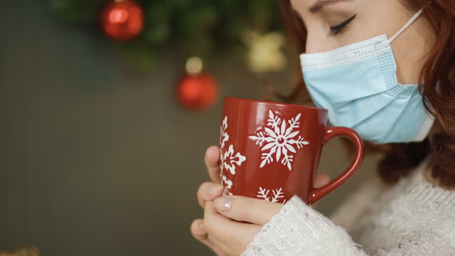 close view: woman in medical mask holds red christmas cup and sniffs - 僅年輕女人 個影片檔及 b 捲影像