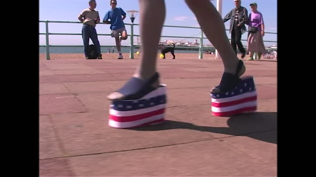 close views of a man walking in stars and stripes platform shoes along the seafront at brighton as he wears drag for pride, uk; 2000. - adult stock videos & royalty-free footage