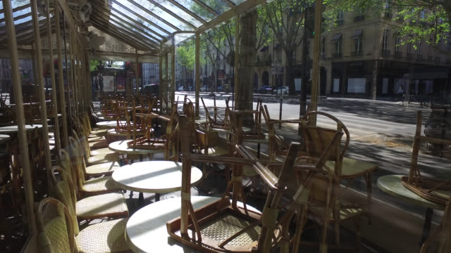 vidéos et rushes de closed bar, table and chairs turned over. one pedestrians, witout traffic on boulevard saint germain. april 15, 2020 in paris, france. the country is... - bar