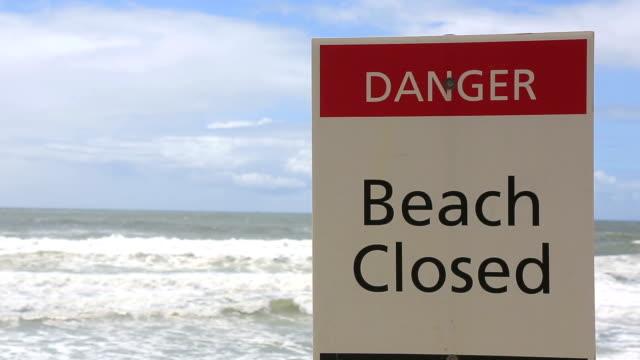 vídeos de stock e filmes b-roll de fechado sinal de perigo de praia numa praia, austrália - sinal de perigo sinal