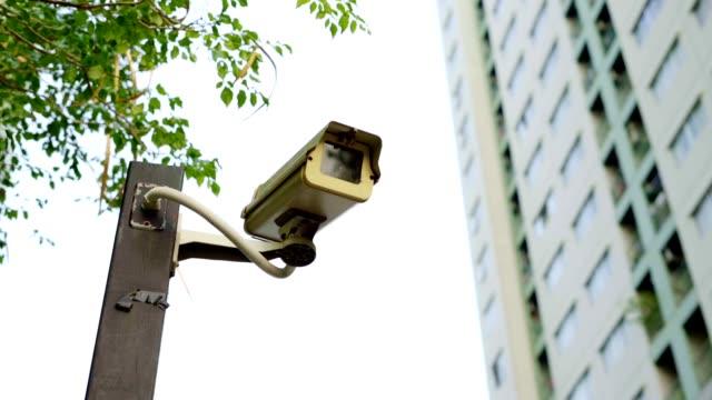 closed circuit camera with building. - telecamera di sorveglianza video stock e b–roll
