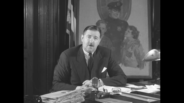 CU closed door with 'Police Commissioner' written on door glass / New York City Police Commissioner Thomas F Murphy sits at desk and addresses camera...