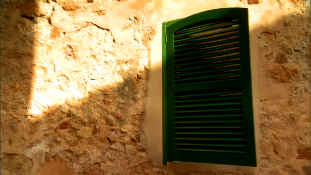 closed green shutters on window of stone house w/ sun streak shining on facade - stone house stock videos & royalty-free footage