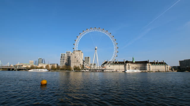 closed london eye, empty victoria embankment and no boats at thames river during lockdown for coronavirus pandemic in london, england, uk, on... - london eye stock-videos und b-roll-filmmaterial