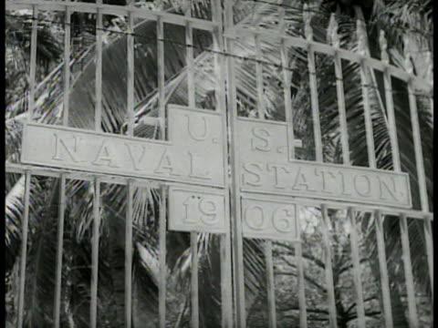 closed naval station gate ls deserted street in naval base neighborhood cu pad lock chain on iron gate - 1934 stock-videos und b-roll-filmmaterial