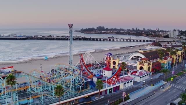 stockvideo's en b-roll-footage met gesloten ritten en kleine oceaan golven op santa cruz beach bij zonsopgang - drone shot - santa cruz californië