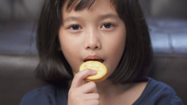 closed up asian young girl enjoy eating cracker at home - cereal plant stock videos & royalty-free footage