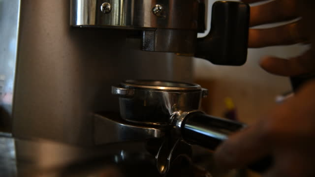 closed up barista making ground coffee with coffee grinder. - cafe macchiato stock videos and b-roll footage