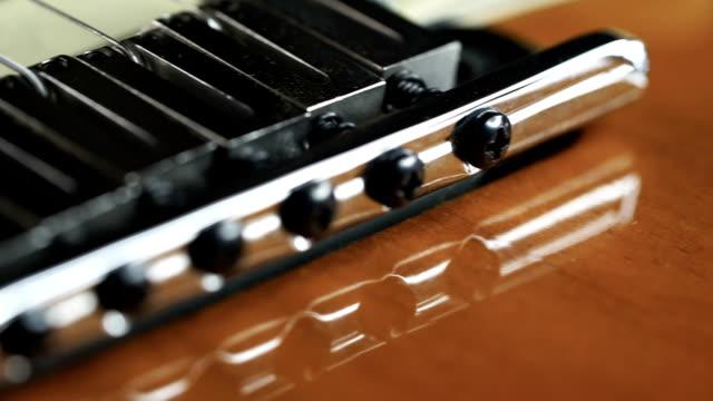Closed up dolly shot of Guitar bridge