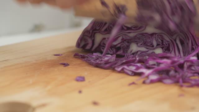 閉じた手でみじん切りにした紫色のキャベツをテーブルに - アブラナ科点の映像素材/bロール