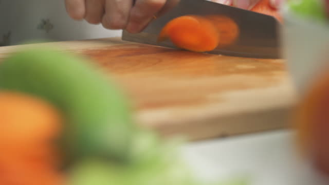 vídeos de stock e filmes b-roll de closed up  hands chopping carrots on wooden cutting board at kitchen - cenoura