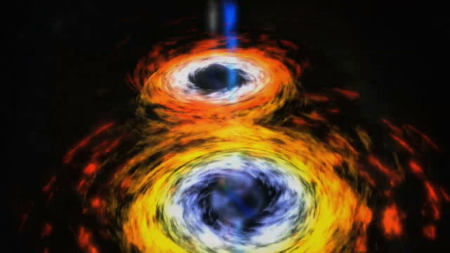 A closer look at the center of a spiral galaxy reveals a pair of black holes locked in a death spiral. When they merge, a massive amount of energy is released in the form of jets