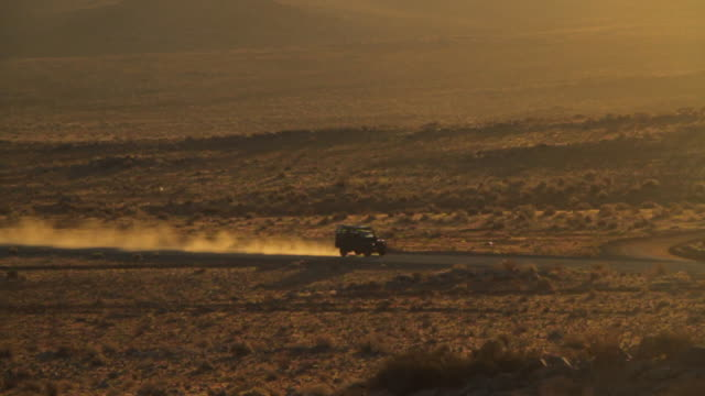 closer shot of land rover defender driving on a long dirt road in the desolate atacama desert mountains at dusk - land rover stock videos and b-roll footage